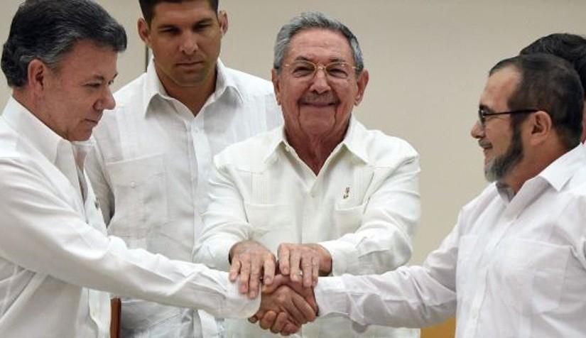 "President Santos (l) and FARC leader ""Timochenko"" shake hands. Atlas . www.elpais.com"